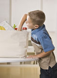 Boy Getting into Groceries Royalty Free Stock Photos
