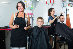 Boy getting hair cut by woman hairdresser Stock Image