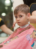 Boy getting a haircut. Boy at hairdresser's during a haircut Royalty Free Stock Photography