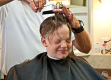 Boy Getting Haircut. This 9 year old Caucasian boy is getting his hair cut from quite long to very short.  Has a facial expression that conveys lots of emotion Stock Photos