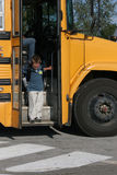 Boy getting off the school bus. Young boy attempting to step off the big step of the yellow school bus Stock Photos