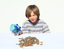 Boy getting out money from saving pig Royalty Free Stock Photo