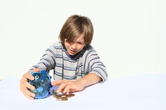 Boy getting out money from saving pig Royalty Free Stock Photography