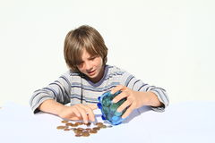 Boy getting out money from saving pig Royalty Free Stock Photos