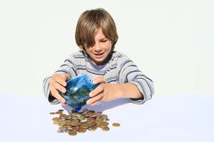Boy getting out money from saving pig Stock Images