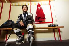 Boy getting ready for hockey game in locker room royalty free stock image