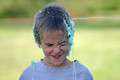 Boy Getting Shot With String. Boys having fun shooting string at each other Royalty Free Stock Photos