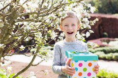 Boy with gift box. Cheerful excited little boy holding gift box for mother's day in the blooming park at spring time Stock Photography