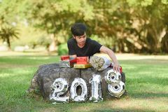 Boy and gift box New Year 2018. Boy and gift box 2018 Number New Year 2018 figure Out door in the garden Stock Photos