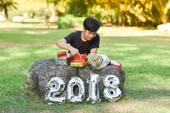Boy and gift box New Year 2018. Boy and gift box 2018 Number New Year 2018 figure Out door in the garden Royalty Free Stock Photo
