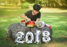 Boy and gift box New Year 2018. Boy and gift box 2018 Number New Year 2018 figure Out door in the garden Royalty Free Stock Image