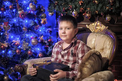 A boy with a gift sitting on a chair Stock Photos