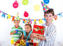 Boy with giftbox at birthday party Stock Images