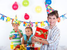Boy with giftbox at birthday party Stock Photo
