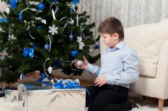 Boy with gifts near  Christmas tree Royalty Free Stock Images