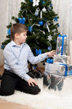 Boy with gifts near  Christmas tree Stock Images