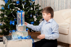 Boy with gifts near  Christmas tree Royalty Free Stock Photography