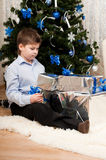 Boy with gifts near  Christmas tree Royalty Free Stock Photo