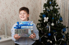 Boy with gifts near  Christmas tree Stock Photos
