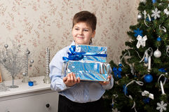 Boy with gifts near  Christmas tree Stock Image
