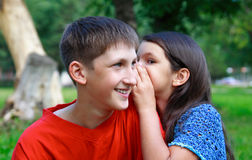 Boy and girl. The girl whispers to the boy a secret outdoors Royalty Free Stock Images