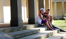 Boy and girl. Two childrens are sitting in front of an old pathway with pillars Royalty Free Stock Images