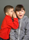 Boy and girl. The boy in a red sweater tells something on an ear Stock Photography