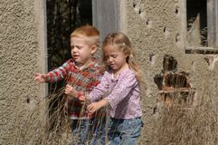 BOY AND GIRL. A three-and-a-half year-old boy and girl – actually twins – examine the tall grass in front of an abandoned, single-room schoolhouse Stock Photo