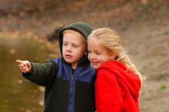Boy and Girl. A young boy and girl dressed in sweatshirts because of the cooler, autumn temperatures watch things float down a river Royalty Free Stock Photo
