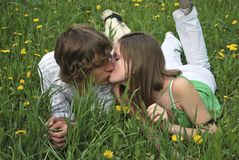 Boy and girl. Beautiful girl and boy on summer lawn with dandelions Stock Photo