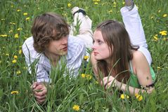 Boy and girl. Beautiful girl and boy on  lawn with dandelions Stock Photos