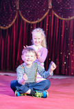 Boy and Girl Acting Silly in Stage Perfomace. Young Boy and Girl Acting Silly in Perfomace on Stage with Bright Lighting and Red Curtain in Background Royalty Free Stock Image