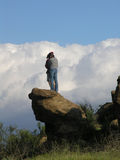 Boy and girl against clouds. Couple view white puffy clouds on rock Royalty Free Stock Images
