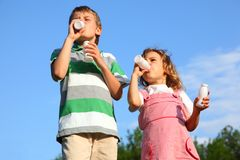 Boy and girl against sky drink yoghurt Stock Images