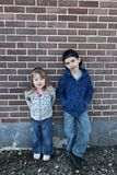 Boy and girl against wall Royalty Free Stock Images