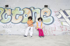 Boy and girl against a wall Royalty Free Stock Images
