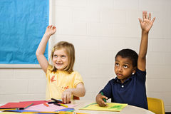 Boy and Girl in Art Class. Boy and Girl raising hands in art class. Horizontally framed shot royalty free stock photo