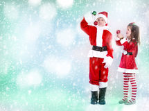 Boy and girl as santa and elf Stock Image