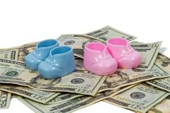 Boy and Girl Baby Booties On a Pile of Money. Horizontal shot of a pair of blue and pink plastic baby booties sitting on a pile of twenty dollar bills on a white Royalty Free Stock Photography
