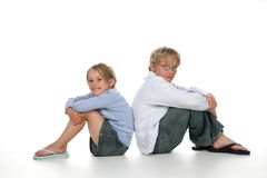 Boy and girl back to back. Cute blond boy and girl sitting back to back with their knees up Stock Photos