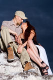 Boy and girl. On the background of sky sitting on a rock Stock Photography