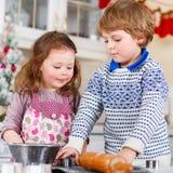 Boy and girl baking Christmas cookies at home Stock Image