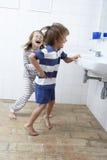 Boy And Girl In Bathroom Brushing Teeth Royalty Free Stock Photography