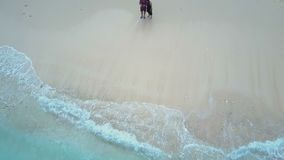 Boy and girl on the beach ocean. Aerial view. Bali. Boy and girl on the beach ocean. Aerial view Bali stock video footage