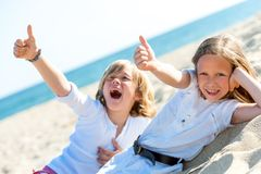 Boy and girl on beach showing thumbs up. Royalty Free Stock Photography