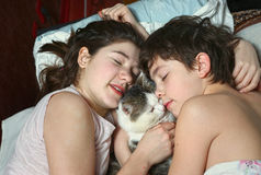 Boy and girl in bed with cat close up portrait Royalty Free Stock Photos