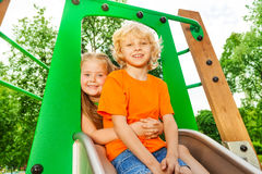 Boy and girl behind hug on chute with smile Stock Photography