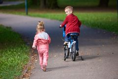 Boy and girl with bicycle Stock Photos