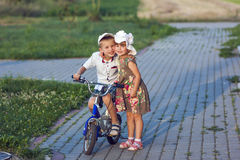 Boy and girl on bicycle playing outdoors on a summer sunny day Stock Photos