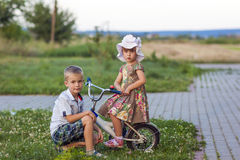 Boy and girl on bicycle playing outdoors on a summer sunny day Royalty Free Stock Photography